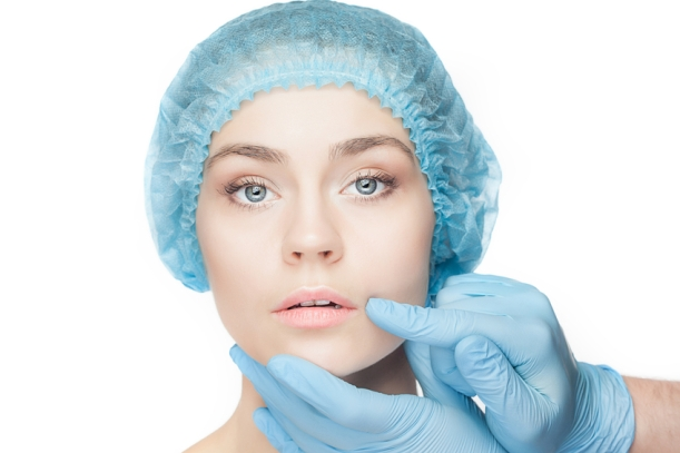 Plastic surgery concept. Doctor hands in gloves touching woman face